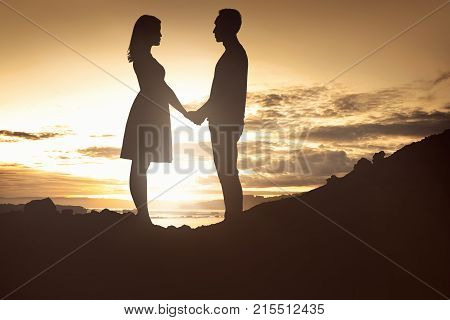 Sillhouette Of A Couple In Love Holding Hands