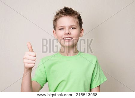 Happy teen boy with removable dental brace showing thumb up gesture