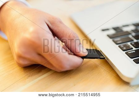 Plugging SD Card into laptop for image file transfer,young woman holding SD Card.