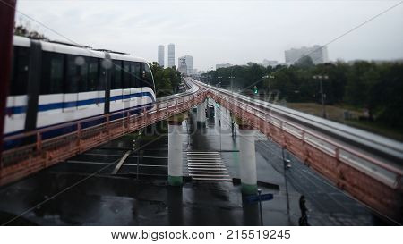 Subway train running outdoors. Footage. Train passes over the bridge over city road in a large metropolis. Subway train on the street.