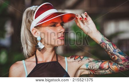 The girl in the red visor looking into the distance. Arms tattooed. Modern beach-ready look