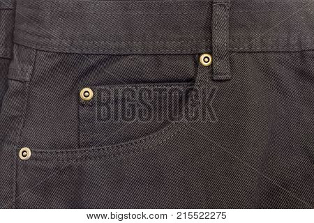 Fragment of the top of the new black jeans with waistband belt loop reinforcing by copper rivets pocket and little pocket