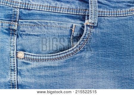 Fragment of the top of the old blue jeans with waistband belt loop reinforcing by copper rivet pocket and little pocket