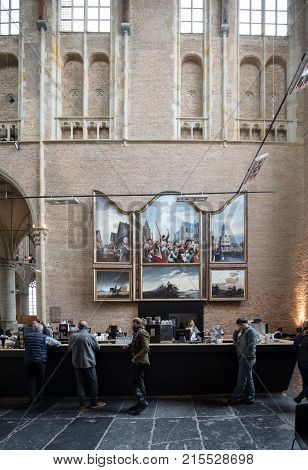 ALKMAAR NETHERLANDS - APRIL 21 2017: people in the cafe inside the Church of St. Lawrence (Grote Kerk or Great Church) in Alkmaar Netherlands.