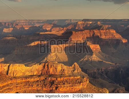 Sunrise over the Grand Canyon, on an early August Morning. The rising sun is casting long dramatic shadows over the Red Rocks of the Canyon. Grand Canyon National Park, Arizona, USA.