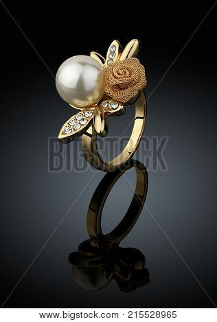 Golden Jewelry ring with pearl on black background