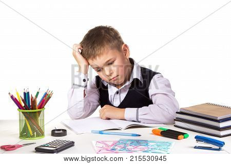 Puzzled bored pupil sitting at the desk with hand under the head surrounded with stationery. poster