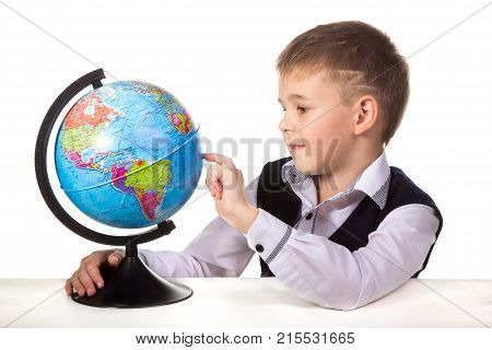 Pupil with a globe. Cheerful satisfied pupil sitting at the desk on the white background.