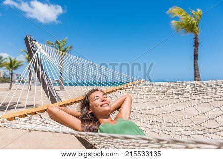 Beach vacation woman happy sleeping in hammock at holiday resort - Caribbean travel holidays Asian girl lying down relaxing outdoors sunbathing.