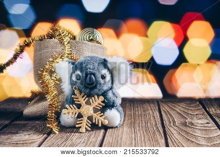 Cute Koala Decorated With Chrismas Decoration Items On Wood And Bokeh Background