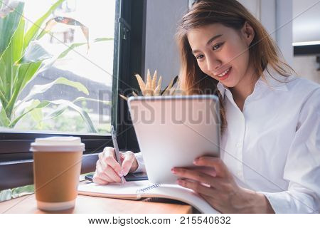Asia casual woman freelancer using tablet and writing plan and smile with coffee cup in cafe restaurantwoman working outside officedigital lifestyle concept