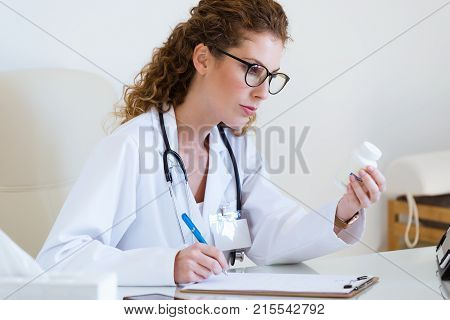 Beautiful Female Pharmacist Holding Jar Of Pills In Hands In The Office.