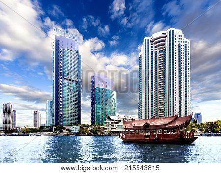 Bangkok city. Skycraper and river Chao phraya.Typical tourist boat
