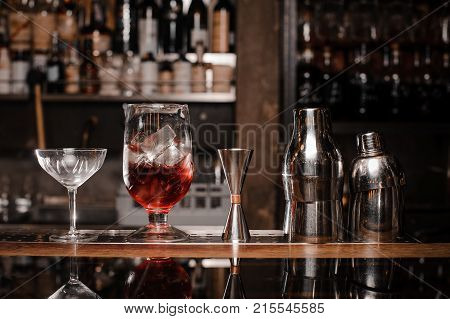 Cocktail glasses filled with alcoholic drink and bar equipment arranged on the bar counter against the shelf of bottles