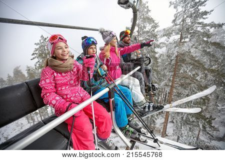 Happy family in ski lift lifting on ski terrain