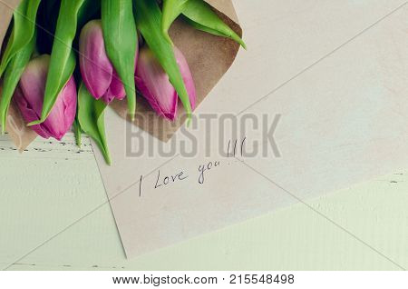 Bouquet of pink tulips with notes I LOVE YOU on white shabby chic background with place for text. Romantic Valentines holidays concept. Valentine's day greeting card. Top view. Copy space.