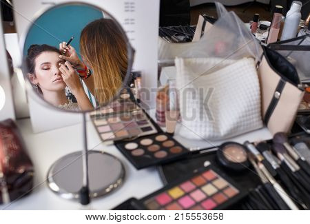 professional makeup artist doing makeup for girl. Make up artist work in beauty salon. Reflection in the mirror as visagist applying makeup. Backstage photo