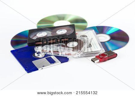 Various media - USB flash drive CD-ROM CD-cassette floppy disks on a white background