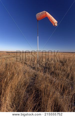 orange windsock in empty prairie grassland, rural Kansas