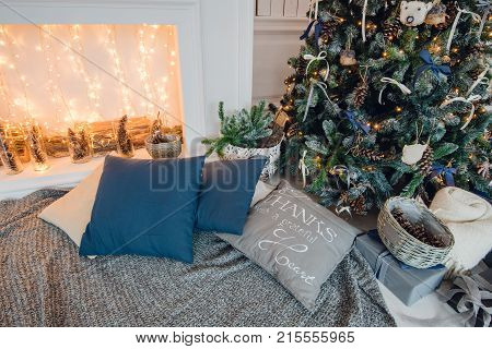 Christmas tree on wooden floor in white interiour. Christmas tree decorates with artificial flowers, garlands and Christmas toys.