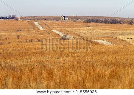 rural Kansas road through tall grass prairie with abandoned stone house