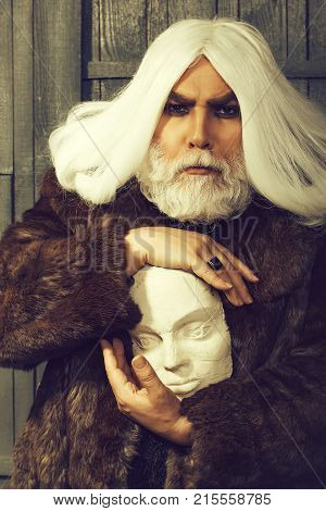 old druid bearded man with long beard on serious face and hair in fur coat holding white sculpture head in hands with ring on wooden background