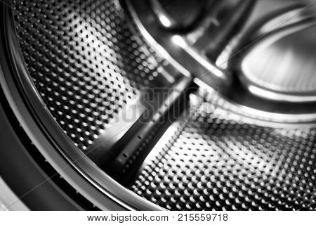 Washing machine drum interior. Perforated stainless steel drum for automatic washing machine. Black and white, metallic background