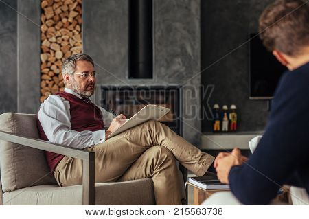 Relationship counselor giving advice to couple at home. Family psychologist consulting conflicted couple.