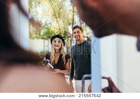 Smiling young couple at entrance door with wine bottle. Friends attending housewarming party.