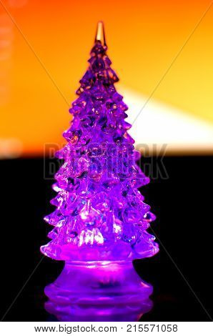 A Small Lighting Christmas Tree On The Contrast Dark And Orange Geometric Background. Selective Focu