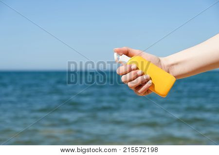 Female Hand Holds The Bottle Against A Sandy Beach And Sea In Bright Sunny Day From Right Side Of Fr
