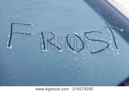 Word frost written on the windshield of frozen car in winter outdoors