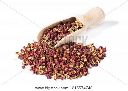 Heap of sichuan chinese pepper with spice shovel isolated on white background