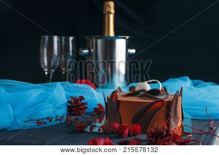 Sweet appetizing beautiful chocolate cake with two crystal glasses of champagne and cooler for champagne on dark background. Cake with blue chiffone for birthday party