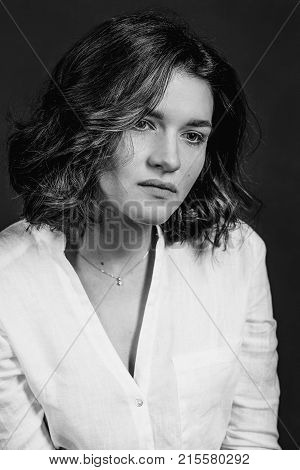 Black and white portraite of young, beautiful sad woman actress with short brown hair in the studio