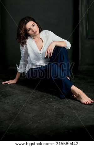 Portraite of young, beautiful sad woman actress with short brown hair in white shirt and blue pants in the studio