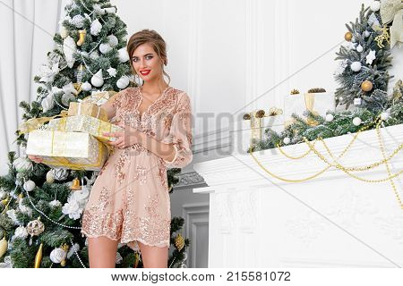 Christmas, winter holidays concept. Beautiful charming woman in evening dress holding a gift box and posing in luxurious apartments decorated for Christmas. Beauty, fashion.