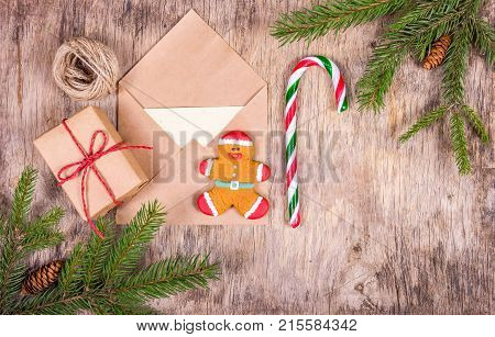 Preparation for Christmas and gift wrapping. Gingerbread man and candy cane on christmas background with fir tree.