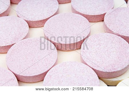 Stack of vitamin mineral supplement effervescent tablets pattern texture. Multivitamin supplement tablet. Soluble Vitamin. Fizzy tablet. Orange flavored effervescent tablets. Closeup.