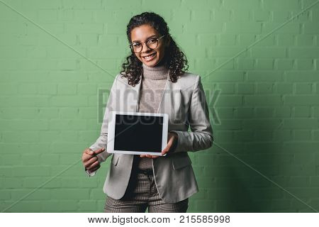 young african american businesswoman presenting digital tablet in front of green wall