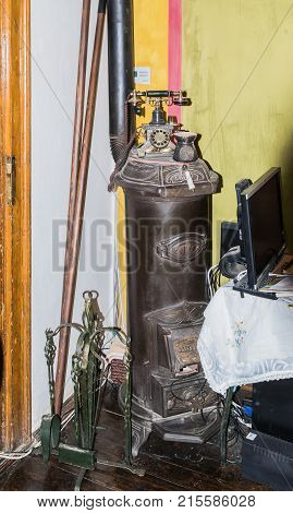 Sighisoara Romania October 08 2017 : Decorative stove and antique telephone standing on it in the corner of the Medieval Cafe in old city. Sighisoara city in Romania