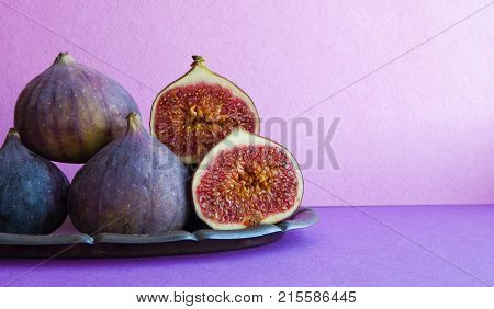 Bright still life organic fig fruits on an old tray, beautiful purple violet background. Selective focus photography, copy space
