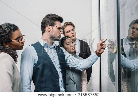 multicultural businesspeople writing on glass board and working in office