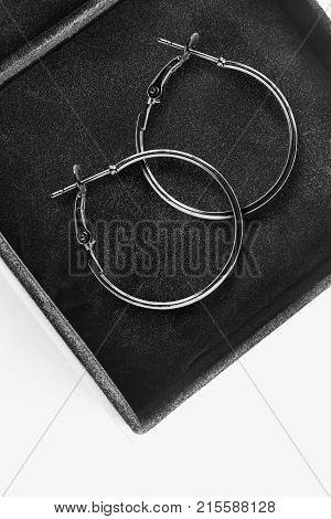 Pair of elegant silver hoops earrings in black jewel box closeup