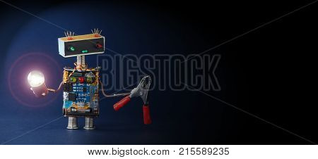 Robot technician lights the way into darkness. Friendly mechanic toy with lamp, red pliers on dark blue background.