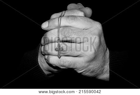 Black and white image of a hands with a cross on a dark background