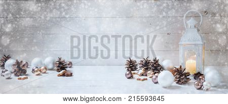 wide christmas background with a candle light lantern baubles cinnamon stars cones and snoe on rustic bright wood panorama format for website banner copy space selected focus