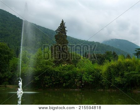Pond with green water. In the center of the pond a fountain in the form of a man shooting from a bow upwards. A stream of water escapes from the arrow. The pond is arranged in an old overgrown park. Around the trees. In the background mountains are overgr
