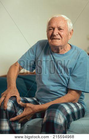Senior man with osteoarthritis pain at home