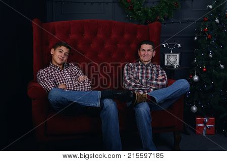 Happy father and teenage son are sitting cross-legged in front of a Christmas tree in anticipation of Christmas.